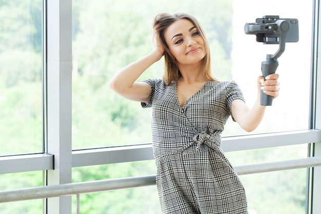 Jeune femme d'affaires enregistrant un blog vidéo sur smartphone au bureau de l'entreprise.