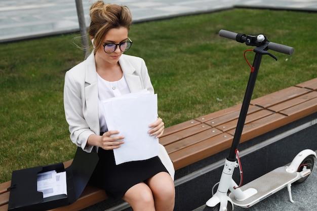 Jeune femme d'affaires est assise sur le banc avec beaucoup de documents papier et scooter électrique à côté d'elle