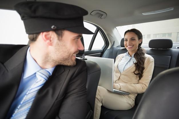 Jeune femme d'affaires étant chauffeur tout en travaillant