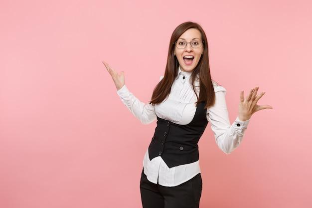 Jeune femme d'affaires étonnée choquée en costume noir et lunettes écartant les mains isolées sur fond rose pastel. dame patronne. concept de richesse de carrière de réalisation. copiez l'espace pour la publicité.