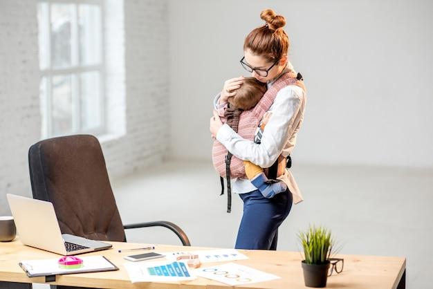 Jeune femme d'affaires étreignant son bébé sur le lieu de travail au bureau