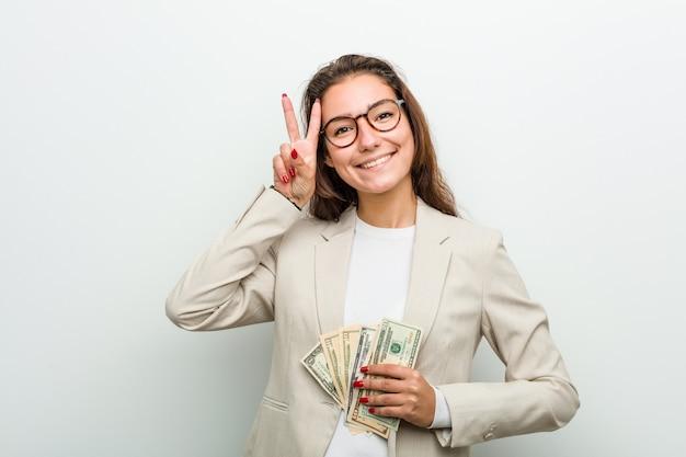 Jeune femme d'affaires européenne détenant des billets de dollar montrant le signe de la victoire et souriant largement.