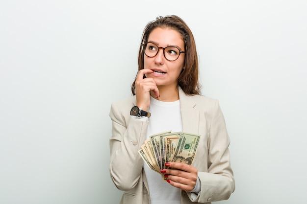 Jeune femme d'affaires européenne détenant des billets en dollars pensée détendue