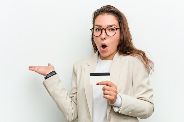 Jeune femme d'affaires européenne détenant une carte de crédit impressionné tenant la surface sur la paume.