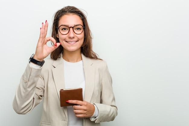 Jeune femme d'affaires européenne tenant un portefeuille joyeux et confiant montrant le geste correct.