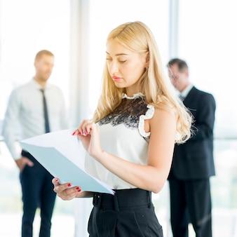 Jeune femme d'affaires examinant des documents