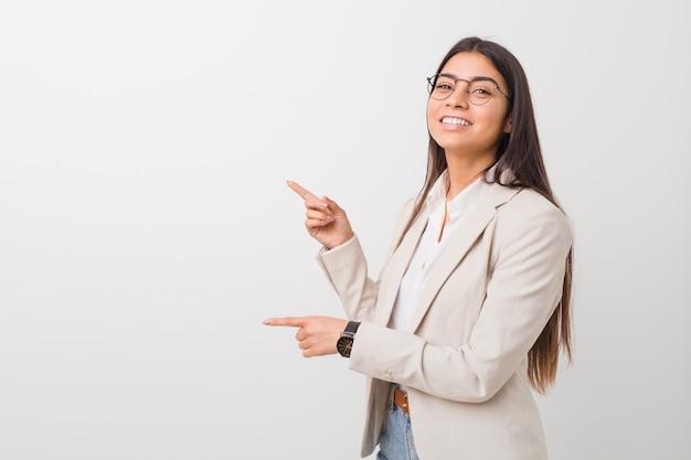 Jeune femme d'affaires excité pointant avec les index loin