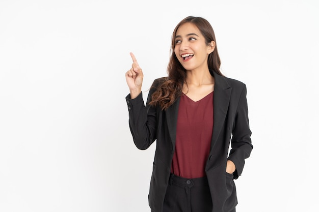 Jeune femme d'affaires excitée avec un geste de la main pointant sur le côté avec fond