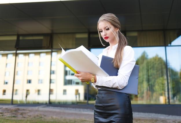Jeune femme d'affaires avec une expression faciale mécontente examine les documents en détail