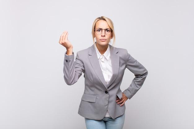Jeune femme d'affaires faisant capice ou geste d'argent, vous disant de payer vos dettes!
