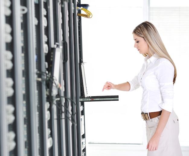 Jeune femme d'affaires féminin avec ordinateur portable moderne dans la salle des serveurs réseau