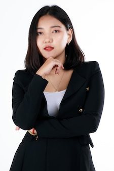 Jeune femme d'affaires fraîche adolescente en costume noir formel sourit avec une vie professionnelle mignonne et sûre d'elle qui commence dans un bureau moderne. concept pour les étudiants nouvellement diplômés et le premier jour de carrière professionnelle.