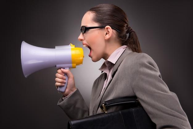 Jeune femme d'affaires avec haut-parleur au concept d'entreprise