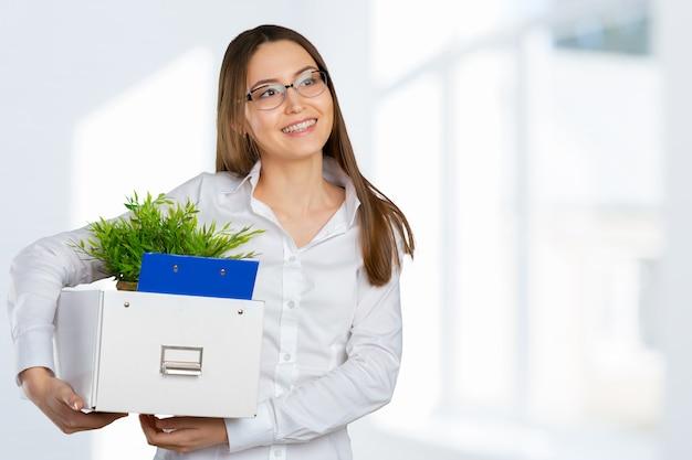 Jeune femme d'affaires heureuse avec une boîte pour passer à un nouveau bureau
