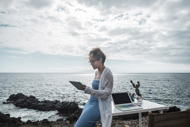 Jeune femme d'affaires heureuse travaillant en plein air dans un bureau alternatif profitant de la nature et de la brise de l'océan