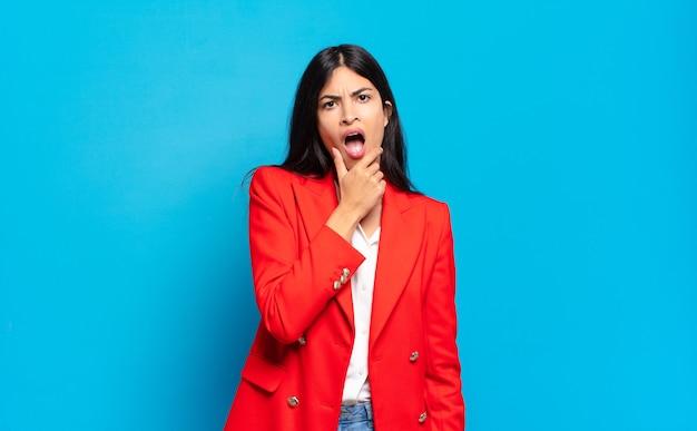 Jeune femme d'affaires hispanique avec la bouche et les yeux grands ouverts et la main sur le menton, se sentant désagréablement choquée, disant quoi ou wow