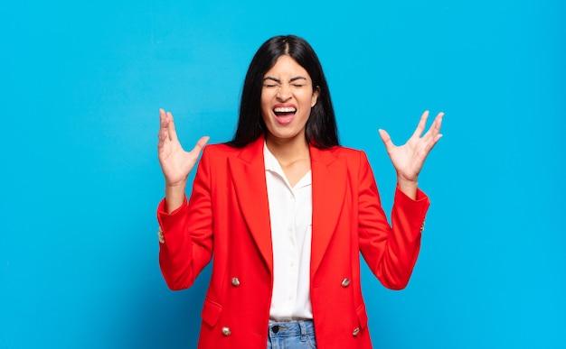 Jeune femme d'affaires hispanique criant furieusement, se sentant stressée et ennuyée avec les mains en l'air disant pourquoi moi