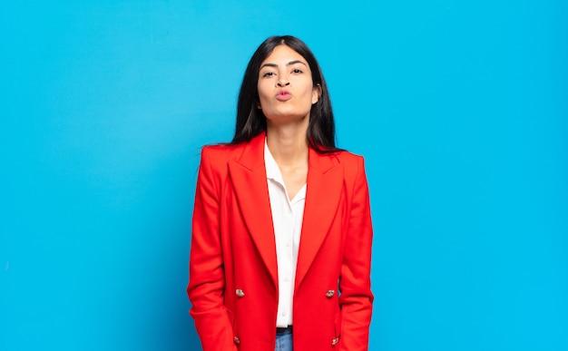 Jeune femme d'affaires hispanique pressant les lèvres ensemble