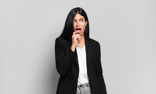 Jeune femme d'affaires hispanique avec un regard surpris, nerveux, inquiet ou effrayé, regardant sur le côté vers l'espace de copie