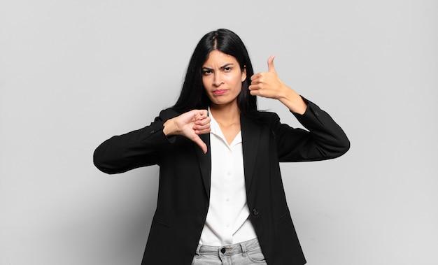 Jeune femme d'affaires hispanique se sentant confuse, désemparée et incertaine, pondérant le bien et le mal dans différentes options ou choix