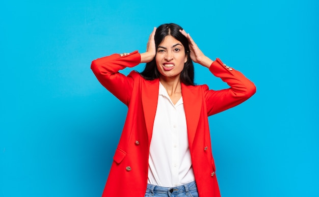 Jeune femme d'affaires hispanique se sentant frustrée et agacée, malade et fatiguée de l'échec, marre des tâches ennuyeuses et ennuyeuses