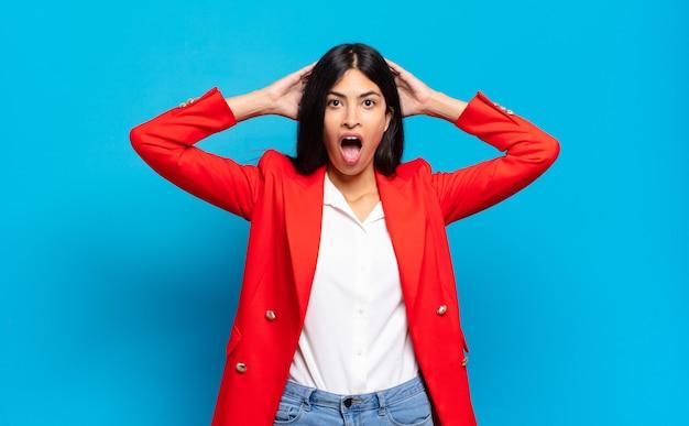 Jeune femme d'affaires hispanique semblant excitée et surprise