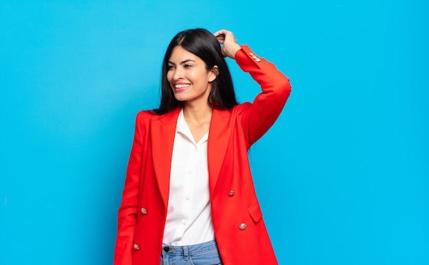 Jeune femme d'affaires hispanique souriant joyeusement et avec désinvolture, prenant la main à la tête avec un regard positif, heureux et confiant