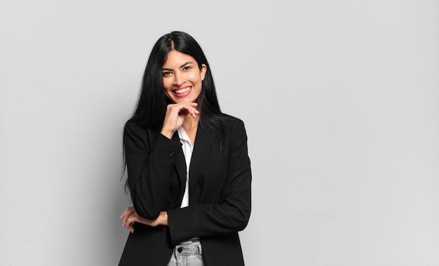 Jeune femme d'affaires hispanique souriant, profitant de la vie, se sentant heureux, sympathique, satisfait et insouciant avec la main sur le menton