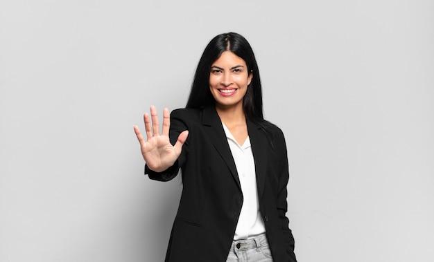Jeune femme d'affaires hispanique souriante et semblant amicale, montrant le numéro cinq ou cinquième avec la main en avant, compte à rebours