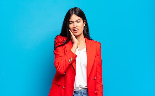 Jeune femme d'affaires hispanique tenant la joue et souffrant de maux de dents douloureux, se sentant malade, misérable et malheureux, à la recherche d'un dentiste