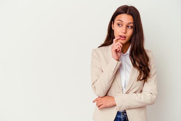 Jeune femme d'affaires indienne isolée sur fond blanc détendue en pensant à quelque chose en regardant un espace de copie.
