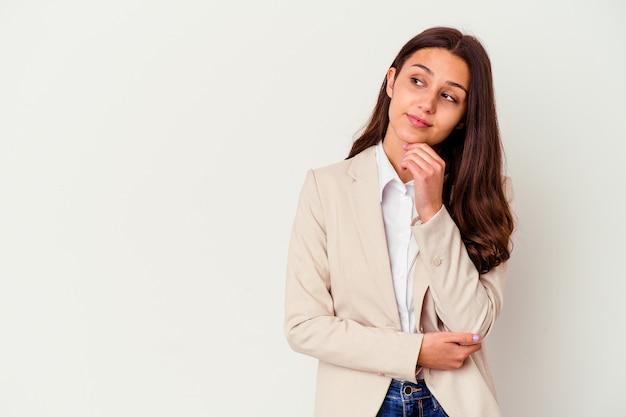Jeune femme d'affaires indienne isolée sur fond blanc à la recherche de côté avec une expression douteuse et sceptique.