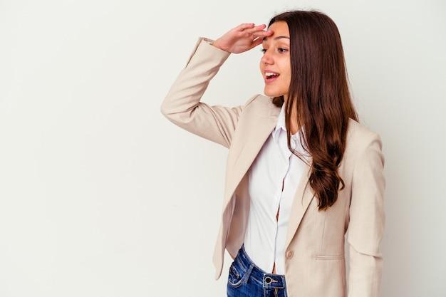 Jeune femme d'affaires indienne isolée sur fond blanc regardant loin en gardant la main sur le front.