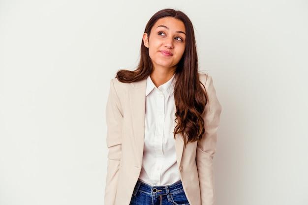 Jeune femme d'affaires indienne isolée sur fond blanc, rêvant d'atteindre les objectifs et les buts