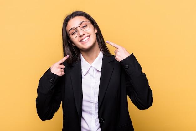 Jeune femme d'affaires indienne isolée sur fond jaune sourit, pointant du doigt la bouche.