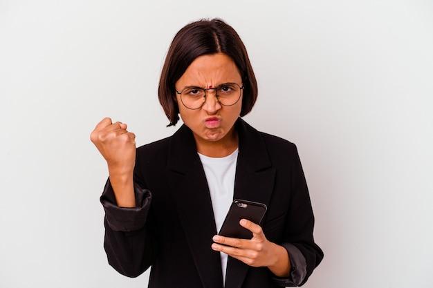 Jeune femme d'affaires indienne tenant un téléphone isolé femme indienne jeune entreprise tenant un téléphone isolé montrant le poing à la caméra, expression faciale agressive.