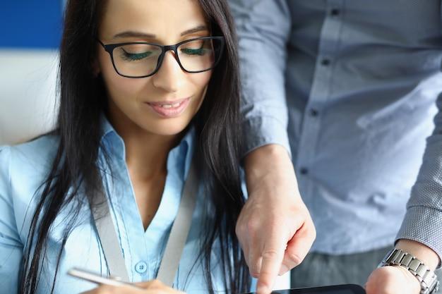Une jeune femme d'affaires introduira une conversation d'affaires avec un collègue de travail