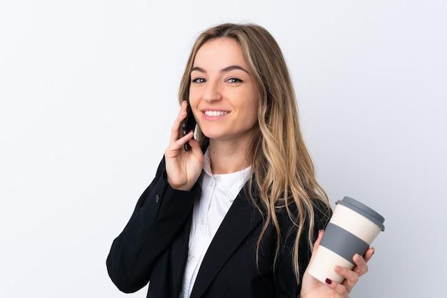 Jeune, femme affaires, isolé, blanc, mur, tenue, tasse, café, téléphone