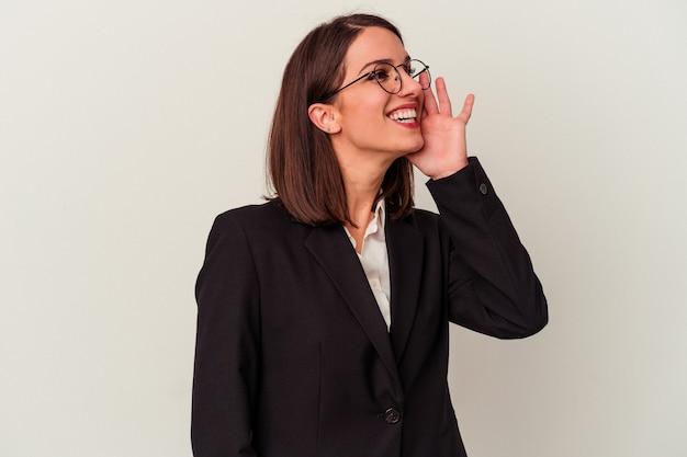 Jeune femme d'affaires isolée sur fond blanc criant et tenant la paume près de la bouche ouverte.
