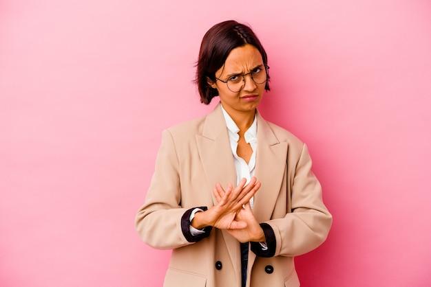 Jeune femme d'affaires isolée sur un mur rose debout avec la main tendue montrant le panneau d'arrêt, vous empêchant