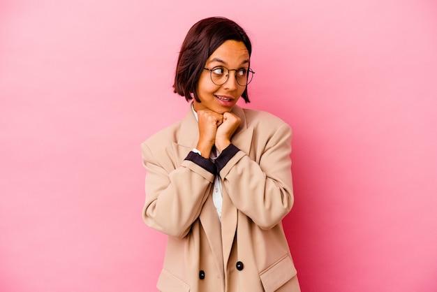 Jeune femme d'affaires isolée sur un mur rose garde les mains sous le menton, regarde joyeusement de côté