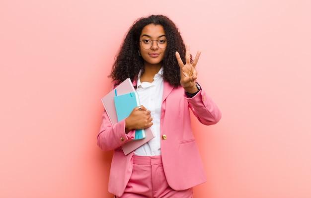 Jeune femme d'affaires jolie noire avec des livres sur fond de mur rose