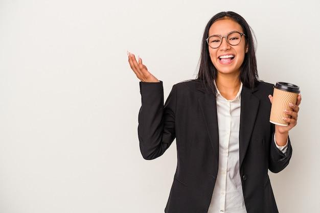 Jeune femme d'affaires latine tenant un café à emporter isolé sur fond blanc recevant une agréable surprise, excitée et levant les mains.
