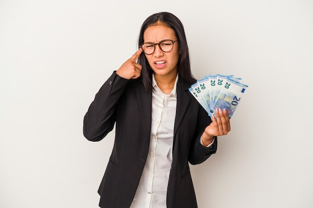 Jeune femme d'affaires latine tenant des factures de café isolé sur fond blanc montrant un geste de déception avec l'index.