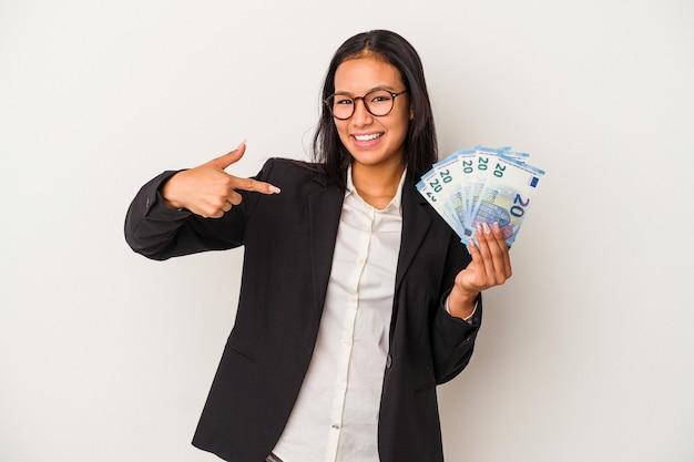 Jeune femme d'affaires latine tenant des factures de café isolé sur fond blanc personne pointant à la main vers un espace de copie de chemise, fière et confiante