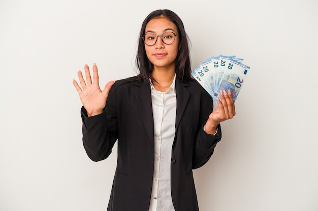 Jeune femme d'affaires latine tenant des factures de café isolé sur fond blanc souriant joyeux montrant le numéro cinq avec les doigts.