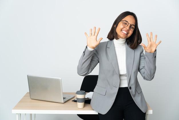Jeune femme d'affaires latine travaillant dans un bureau isolé sur blanc en comptant dix avec les doigts