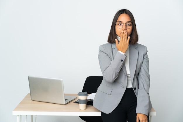 Jeune femme d'affaires latine travaillant dans un bureau isolé sur blanc couvrant la bouche avec la main