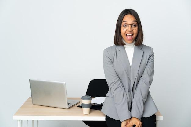 Jeune femme d'affaires latine travaillant dans un bureau isolé sur blanc avec une expression faciale surprise