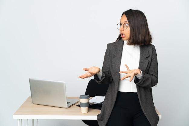 Jeune femme d'affaires latine travaillant dans un bureau isolé sur blanc avec une expression de surprise tout en regardant côté